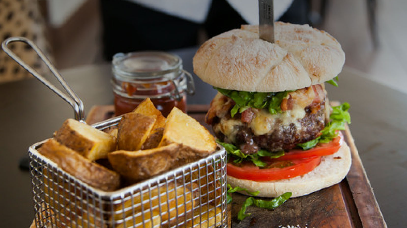 Knife in beef burger with chunky chips