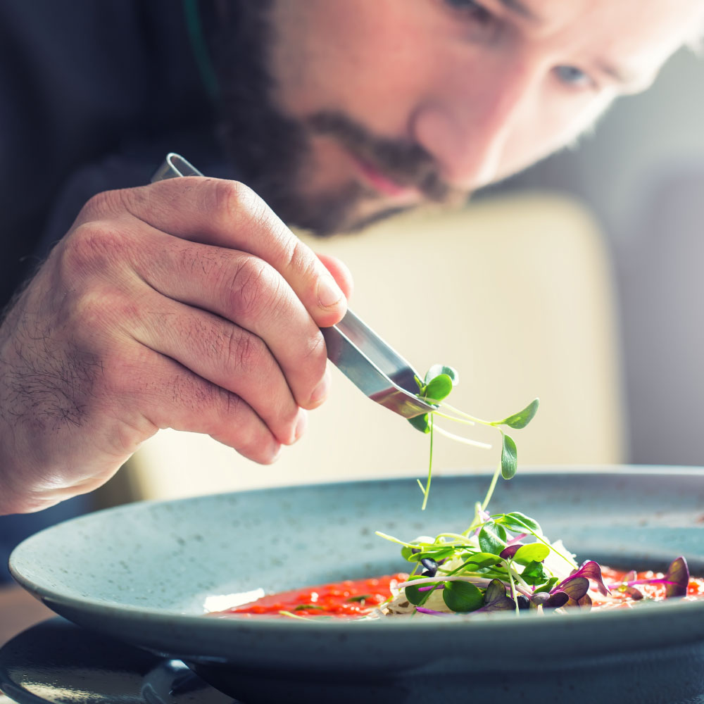 Chef adding garnishing to a dish